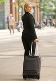 Mujer de negocios que viaja con la maleta en la ciudad Fotografía de archivo libre de regalías