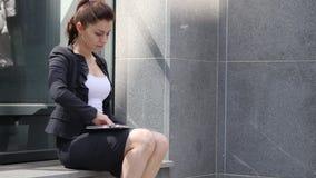 Mujer de negocios que viene y que se sienta fuera de oficina y que trabaja en el ordenador portátil almacen de metraje de vídeo