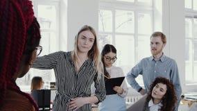 Mujer de negocios rubia atractiva joven que da direcciones al equipo en la EPOPEYA ROJA ligera moderna de la cámara lenta del sem almacen de video