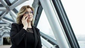 Mujer de negocios rubia atractiva usando el viajero de Smartphone en ciudad, mujer de negocios joven bonita que habla por el telé almacen de video