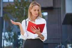 Mujer de negocios rubia decepcionada con el cuaderno contra del edificio de oficinas fotos de archivo libres de regalías