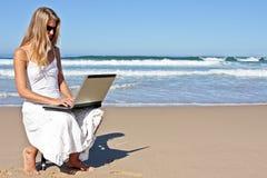 Mujer de negocios rubia joven que trabaja en su computadora portátil Foto de archivo