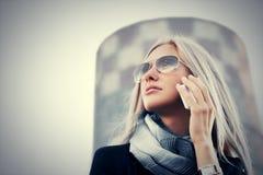 Mujer de negocios rubia de moda en gafas de sol que habla en el teléfono móvil Imagen de archivo libre de regalías