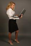 Mujer de negocios rubia que pulsa en la computadora portátil Imagenes de archivo