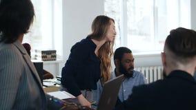 Mujer de negocios rubia sonriente feliz de la diversi?n positiva que lleva el seminario interactivo para los trabajadores multi?t almacen de metraje de vídeo