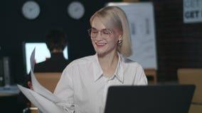 Mujer de negocios satisfecha que disfruta el ordenador portátil delantero de los buenos resultados en oficina oscura almacen de video