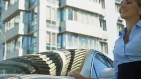 Mujer de negocios satisfecha que frota ligeramente el nuevo automóvil con el amor, compra acertada almacen de metraje de vídeo