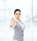 Mujer de negocios seria que hace la muestra de la mano de la parada foto de archivo