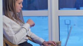 Mujer de negocios seria que mecanografía en un ordenador portátil en un pasillo del hotel almacen de metraje de vídeo