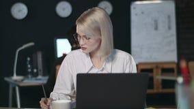 Mujer de negocios seria que trabaja con el documento financiero en última oficina metrajes