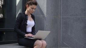 Mujer de negocios seria que trabaja en el ordenador portátil fuera de la oficina almacen de video