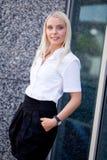 Mujer de negocios sonriente acertada joven atractiva que se coloca al aire libre Foto de archivo