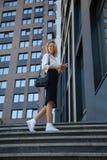 Mujer de negocios sonriente con el bolso y teléfono celular contra el edificio de oficinas imagenes de archivo