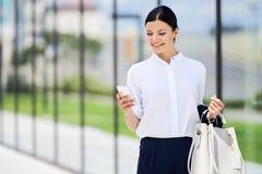 Mujer de negocios sonriente con el mensaje de texto de la lectura del bolso Imágenes de archivo libres de regalías
