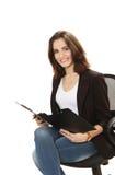 Mujer de negocios sonriente con la carpeta y la pluma en cha de la oficina Imágenes de archivo libres de regalías