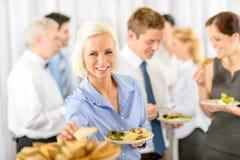 Mujer de negocios sonriente durante comida fría del almuerzo de la compañía Imágenes de archivo libres de regalías