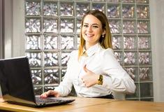 Mujer de negocios sonriente hermosa que muestra los pulgares para arriba al lado de su ordenador portátil Imagen de archivo libre de regalías