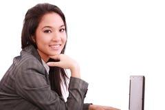 Mujer de negocios sonriente hermosa que trabaja en la computadora portátil Imagen de archivo