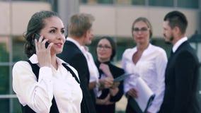 Mujer de negocios sonriente joven que discute su día laborable acertado en el teléfono y sus colegas que charlan en metrajes