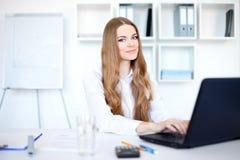Mujer de negocios sonriente joven que trabaja en la computadora portátil Fotografía de archivo