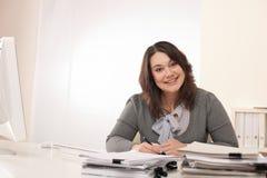 Mujer de negocios sonriente joven que trabaja en la oficina Imagen de archivo