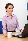 Mujer de negocios sonriente que come café en su escritorio Imagen de archivo libre de regalías