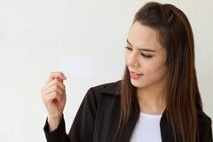 Mujer de negocios sonriente que mira la tarjeta en blanco Fotos de archivo libres de regalías