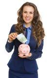 Mujer de negocios sonriente que pone el billete de banco del euro 100 en la hucha Imágenes de archivo libres de regalías