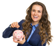 Mujer de negocios sonriente que pone la moneda en la hucha Foto de archivo