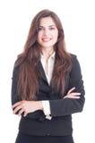 Mujer de negocios sonriente que se coloca con los brazos cruzados Imágenes de archivo libres de regalías