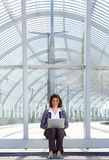 Mujer de negocios sonriente que se sienta afuera usando el ordenador portátil Imagen de archivo libre de regalías