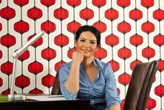 Mujer de negocios sonriente que se sienta en el escritorio Imágenes de archivo libres de regalías