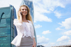 Mujer de negocios sonriente que tiene conversación agradable sobre el teléfono móvil Foto de archivo libre de regalías