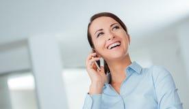 Mujer de negocios sonriente que tiene una llamada de teléfono Imágenes de archivo libres de regalías