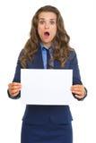 Mujer de negocios sorprendida que muestra la hoja del papel en blanco Imagenes de archivo
