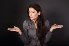 Mujer de negocios subrayada infeliz de la confusión que gesticula las manos ab Foto de archivo