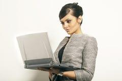 Mujer de negocios triguena con la computadora portátil Imágenes de archivo libres de regalías