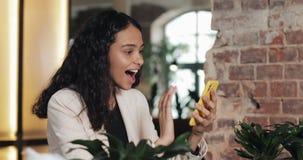 Mujer de negocios usando el app en el smartphone que se sienta en oficina moderna Profesional femenino casual hermoso en traje ro metrajes