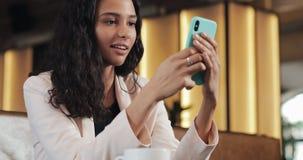 Mujer de negocios usando el app en el smartphone que se sienta en oficina moderna Profesional femenino casual hermoso en traje ro almacen de video
