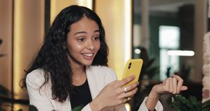 Mujer de negocios usando el app en el smartphone que se sienta en oficina moderna Profesional femenino casual hermoso en traje ro almacen de metraje de vídeo