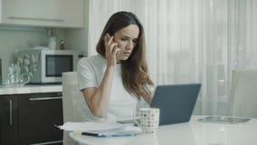 Mujer de negocios usando el ordenador port?til en casa Tel?fono m?vil de la llamada profesional metrajes
