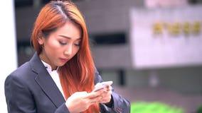 Mujer de negocios usando móvil en la calle metrajes