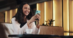Mujer de negocios usando smartphone en café de consumición del café que ríe en café Comunicación, negocio acertado, fechando almacen de metraje de vídeo