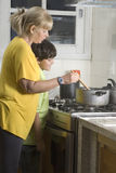 Mujer de observación del muchacho cocinar - vertical imagen de archivo libre de regalías