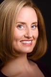 Mujer de ojos azules sofisticada que sonríe a la cámara Fotos de archivo libres de regalías