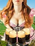 Mujer de Oktoberfest que sostiene cuatro tazas de cerveza Imagen de archivo