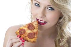 Mujer de Oung que come la rebanada de la pizza Foto de archivo libre de regalías