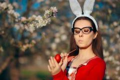 Mujer de Pascua con Bunny Ears Painting y el adornamiento de los huevos rojos Imagenes de archivo