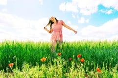 Mujer de pelo largo en un vestido rosado en un campo del trigo verde y de las amapolas salvajes imagenes de archivo