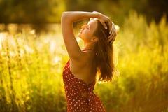 Mujer de pelo largo feliz en la puesta del sol en el campo Imágenes de archivo libres de regalías